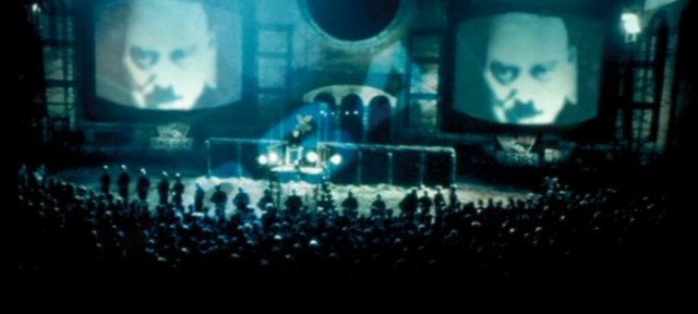 Big Brother's face looms from giant telescreens in Victory Square in Michael Radford's 1984 film adaptation of George Orwell's Nineteen Eighty-Four. (from here)